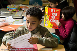 Education Elementary school Grade 2 foreign language male student working on Spanish language worksheet horizontal