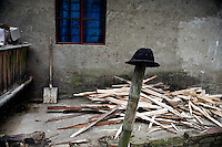 A man's hat rests on a fence post during work outside a small house in Pangzhihua Village, Yuanyang County, Yunnan Province, China.