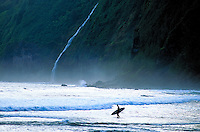 Surfer on the beach at Waipio with stunning waterfall on the lush coastline of the Big Island of Hawaii.