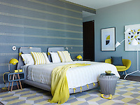 A bold guest bedroom decorated in tones of yellow and grey has a strong retro feel reflected in the furniture and patterning.