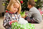 Girl (6-7) wrapping Christmas present