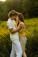 Young couple embracing in open field