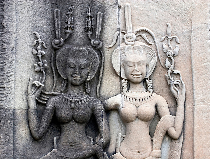 Stone carved bas relief of two smiling Apsaras (celestial maidens) at Angkor Wat, built in the 11th century by Suryavarman the 2nd,  -  Cambodia..
