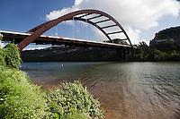 Boaters pass underneath the 360 Bridge (Pennybacker Bridge) surrounding hills and lake austin, Texas, USA