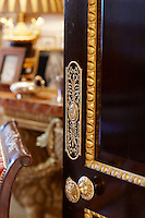 A detail of decorative gilded moulding on a wooden door with a gilt door handle and doorplate.