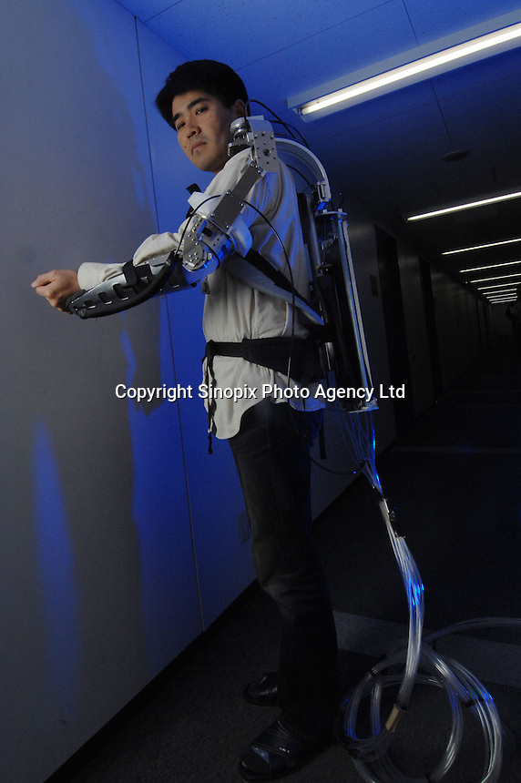 """Dr Hiroshi Kobayashi poses with his """"Muscle Suit"""" at the Department of Mechanical Engineering, Tokyo University of Science. The Muscle Suit is a suit that will enable people who are disabled to move their limbs."""