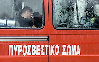 A firefighter rests in a fire service bus in Nea Mihaniona