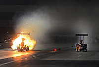 Nov. 10, 2012; Pomona, CA, USA: NHRA top fuel dragster driver Antron Brown (left) explodes an engine alongside Clay Millican during qualifying for the Auto Club Finals at at Auto Club Raceway at Pomona. Mandatory Credit: Mark J. Rebilas-