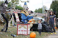 Bella Harrison-Rackley, 10, watches Thursday, October 15, 2020, her brother Noah Bohannan, 2, react to Halloween decorations at a home on Backus Avenue in Springdale. Julie Farr, babysitter, said that visiting the decorated house is a favorite activity of Noah's and he likes to talk to the different characters. Check out nwaonline.com/201016Daily/ and nwadg.com/photos for a photo gallery.(NWA Democrat-Gazette/David Gottschalk)