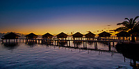 Sunset over a line of lit-up overwater bungalows reflecting on the lagoon in honeymoon Huahine island, near Tahiti, Polynesia, Pacific Ocean