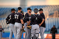 Charlotte Knights pitching coach Steve McCatty (54) talks with pitcher Justin Nicolino and catcher Seby Zavala during an International League game against the Syracuse Mets on June 11, 2019 at NBT Bank Stadium in Syracuse, New York.  Syracuse defeated Charlotte 15-8.  (Mike Janes/Four Seam Images)