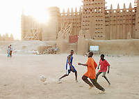 Boys play soccer in the main square outside the Great Mosque of Djenné, the worlds largest mud built structure and UNESCO heritage site, at Djenné, Mali