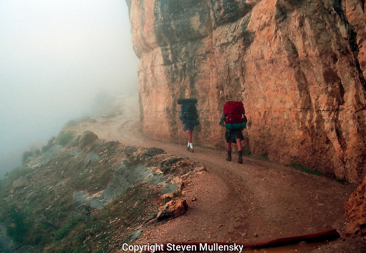 Hikers start down the fog covered Bright Angel Trail on the south rim of the Grand Canyon.