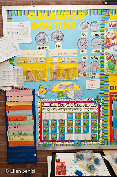 Schenectady, New York. Zoller Elementary School (urban public school). First Grade Inclusion class. Bulletin board display shows classroom daily calendar routine. Students use this display to review the date, weather, classroom schedule, and go over current math concepts - here, about money. ID: AJ-g1b. ©Ellen B. Senisi