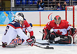Sochi, RUSSIA - Mar 13 2014 - Declan Farmer takes a shot on Corbin Watson as Canada takes on USA in Sledge Hockey Semi-Final at the 2014 Paralympic Winter Games in Sochi, Russia.  (Photo: Matthew Murnaghan/Canadian Paralympic Committee)