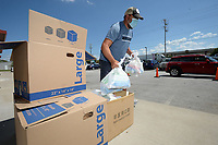 """Doug Allen, owner of Jose's Bar and Grill, carries bags of supplies Friday, Aug. 21, 2020, as he hands out boxes of personal protective equipment to Northwest Arkansas teachers at the restaurant in Tontitown. Allen raised about $13,000 to provide hand sanitizer, masks and cleaning supplies for teachers. """"We've got an assortment of stuff for them to help them outfit their classroom, put their mind at ease and let the community know we care about our teachers,"""" Allen said. Visit nwaonline.com/200823Daily/ for today's photo gallery.<br /> (NWA Democrat-Gazette/Andy Shupe)"""