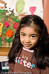 Education preschoool children ages 3-5 closeup portrait of girl vertical painting on wall behind her