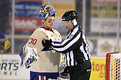 Rochester Amerks goalie Matt Hackett (30) talks to linesman Jeff Walker (28) after allowing a goal with .01 seconds left in the third period of The Frozen Frontier outdoor AHL game against the Lake Erie Monsters at Frontier Field on December 13, 2013 in Rochester, New York.  (Copyright Mike Janes Photography)