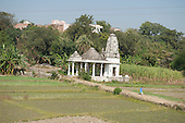 India; road from Udaipur to Jodhpur. A small roadside Hindu temple with a girl in school uniform in fields.