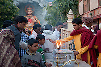 India, Rishikesh.  Monk Giving Blessing to Young Boy after Evening Prayer (Aarti) at the Parmarth Niketan Ashram.  Hanuman Shrine in Background.