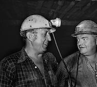 Sangerhausen / DDR - 1989.Miniera di rame Thomas Munzer. 700 metri di profondità. Minatori al lavoro nelle gallerie sul fronte della miniera.Le gallerie erano alte un metro. Le ginocchia affondavano nel fango. Le squadre di minatori lavoravano 24 ore suddivisi in turni di 8 ore. A causa delle dure condizioni di lavoro, numerosi operai si ammalavano di silicosi e reumatismi ed andavano in pensione in anticipo. In compenso i loro stipendi erano i più alti della DDR. Dopo la reunificazione della Germania la miniera Thomas Munzer è stata chiusa..Foto Livio Senigalliesi..Sangerhausen / DDR - Dec.1989.Thomas Munzer copper mine. In a tunnel 700 meters depth. Workers on board a small train that brought them to work on the front of the mine. Working conditions were very hard. They worked on their knees in the dark using the lamp of acetylene. Teams of miners worked 8 hours in 3 shifts. After the unification of Germany Thomas Munzer copper mine was closed and has now become a museum..Photo Livio Senigalliesi.