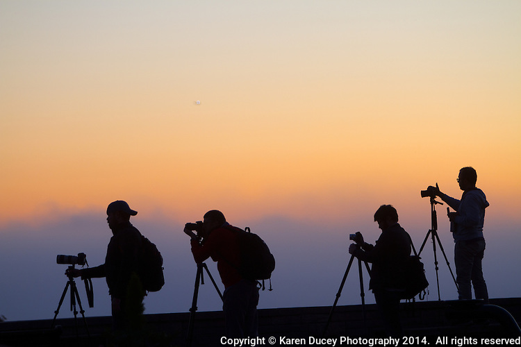 Silhouette of photographer's with tripods and cameras with the sunset in the background.