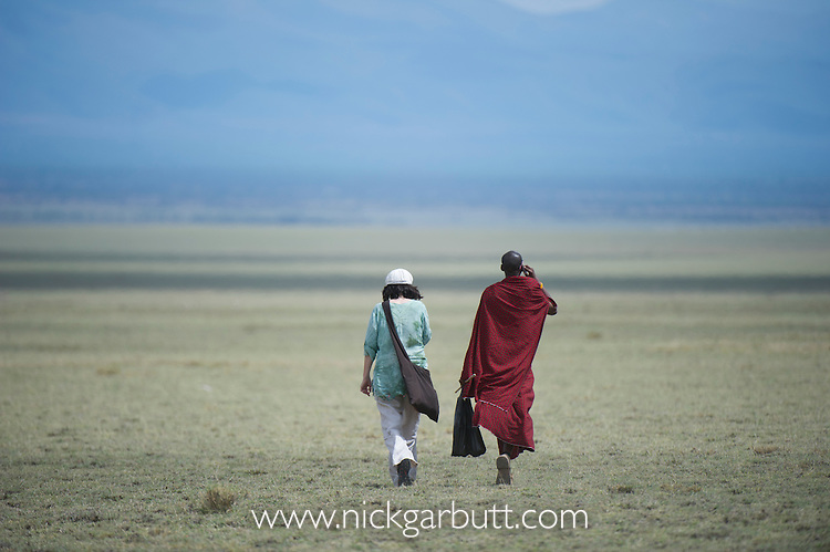 Maasai man walking with Western foreigner across the plains near the Great Rift Valley. Ngorongoro Conservation Area, Tanzania.