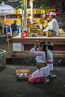 Bali, Indonesia.  Young Women Praying in Hindu Temple.  Priest Sits on Platform, Upper Right.  Pura Dalem Temple, Dlod Blungbang Village.