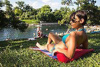 Attractive young woman in a blue bikini sunbathes on the rolling green hills next to Barton Springs Pool, Austin, Texas