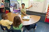 MR / Schenectady, NY. Zoller Elementary School (urban public school). Kindergarten classroom. Paraprofessional (Puerto Rican American) teaches Spanish-language lesson to bilingual students. Left: boy, 6, African American /  Puerto-Rican American; Right: girl, 5; both are native Spanish speakers. MR: Pac1, Car38, Cas12. ID: AM-gKw. © Ellen B. Senisi.
