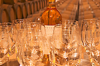 Wine tasting in the cellar, glasses, a bottle and barrels in the background - Chateau Haut Bergeron, Sauternes, Bordeaux