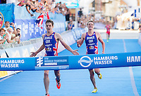 20 JUL 2013 - HAMBURG, GER - Jonathan Brownlee (GBR) (left) of Great Britain celebrates winning the elite men's ITU 2013 World Triathlon Series race ahead of his brother Alistair Brownlee (GBR) (right) also of Great Britain in Hamburg, Germany (PHOTO COPYRIGHT © 2013 NIGEL FARROW, ALL RIGHTS RESERVED)