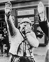 """Title: The tragedy of this Sudeten woman, unable to conceal her misery as she dutifully salutes the triumphant Hitler, is the tragedy of the silent millions who have been """"won over"""" to Hitlerism by the """"everlasting use"""" of ruthless force., ca. 1938"""