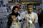 Palestinian artists Samah Said and Dorgham Krakeh  paint N95 protective masks for a project raising awareness about the COVID-19 coronavirus pandemic, in Gaza City on March 24, 2020. Photo by Osama Baba