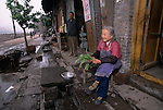 Senior woman sits in front of home cleaning leafy vegetable on street in old Fengdu; to be razed  for 3 Gorges Dam project; China, Asia; 041803