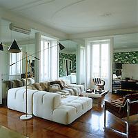 A vintage Arredoluce Triennale floor lamp illuminates the elegant white Patrica Urquioia sofa in the living room