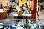 A shopper checks watches at a stall at the Pavilion, a high end shopping mall in Kuala Lumpur, Malaysia.