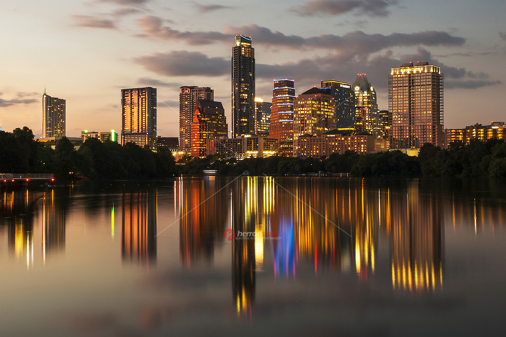 A new image photographed from the Boardwalk Trail Bridge of the beautiful Austin skyline cityscape at night, reflected on Ladybird Lake.