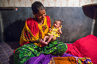 "India; Maharashtra; Mumbai; Bombay, the red light district, Kamatipura.<br /> Puja is a sex-worker here in the brothel with her new-born baby that is about two days old. This is her fifth child, earlier in the week we found her four children running around the street unsupervised. She has a ""husband,"" client but she also services about ten customers a day so she's never really sure who the fathers are. Often the children stay in a shelter but the shelters only care for them for twelve hours at a time so she tends to have them in the shelter at night when she's working. She keeps having children because she really wants a boy. She had a boy once but he was eaten by a rat in the brothel and died. This latest baby she is holding is a girl."