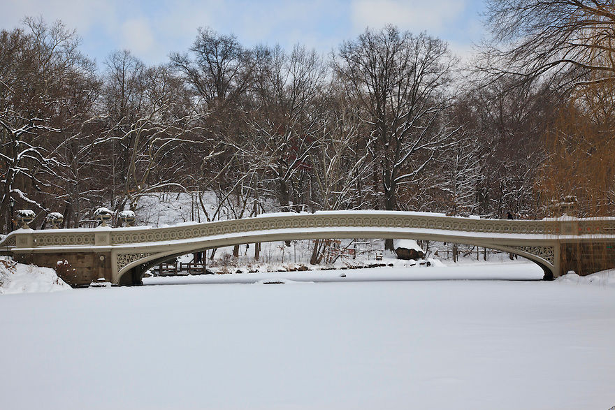 Bow Bridge in New York City's Central Park covered with snow.<br /> Frozen lake in foreground.