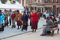 Bodhnath, Nepal.  Pilgrims and visitors circumambulate the stupa (on their right) in a clockwise direction, especially in late afternoon hours.  Many finger prayer bead rosaries.