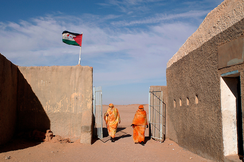 Two women get into a hospital in the wilaya of Ausserd on December 13, 2003. Saharawi people have been living at the refugee camps of the Algerian desert named Hamada, or desert of the deserts, for more than 30 years now. Saharawi people have suffered the consecuences of European colonialism and the war against occupation by Moroccan forces. Polisario and Moroccan Army are in conflict since 1975 when Hassan II, Moroccan King in 1975, sent more than 250.000 civilians and soldiers to colonize the Western Sahara when Spain left the country. Since 1991 they are in a peace process without any outcome so far. (Ander Gillenea / Bostok Photo)
