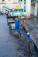 Cycle rickshaw parked near a street market in Santa Clara, Villa Clara, Cuba.