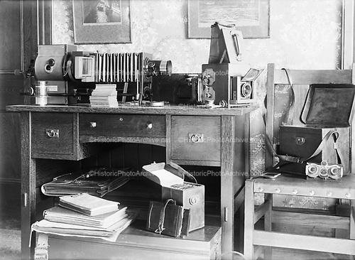 0405-C01 Photographer's desk.  Equipment includes a Bausch & Lomb Model C Balopticon lantern slide projector, Graflex camera, lenses for a Blair Kodak Stereo Hawkeye #4.