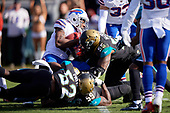 Jacksonville Jaguars Lerentee McCray (55), Carroll Phillips (59), and Donald Payne (52) tackle returner Brandon Tate (15) during an NFL Wild-Card football game against the Buffalo Bills, Sunday, January 7, 2018, in Jacksonville, Fla.  (Mike Janes Photography)