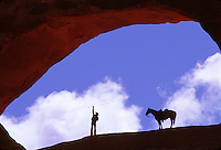 The silhouettes of a cowboy twirling a lasso and horse, framed by an arched rock formation; high color contrast with blue sky and clouds.