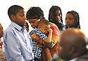 Ashaun Cotton,  Debera Jefferson, holding her grandson Angelito Estrado, and  her two granddaughters Dominique and Destiny Patterson listen while Rev. Aldon Cotton preaches to his congregation about surviving day to day after Hurricane Katrina, New Orleans, Sun., Aug. 27, 2006.<br />(Cheryl Gerber for USA Today)