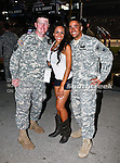 A beautiful girl poses with some soldiers during the Samsung Mobile 500 Sprint Cup race at Texas Motor Speedway in Fort Worth,Texas.