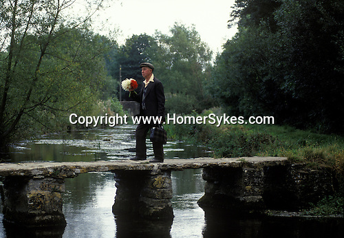 Eastleach Turville, Gloucestershire. 1993<br /> Long time countryman Albert Waring who has lived in the village all his life crosses the River Leach by way of the medieval clapper bridge, he carries a bouquet of home grown Dahlias that he will place on his wife's grave.