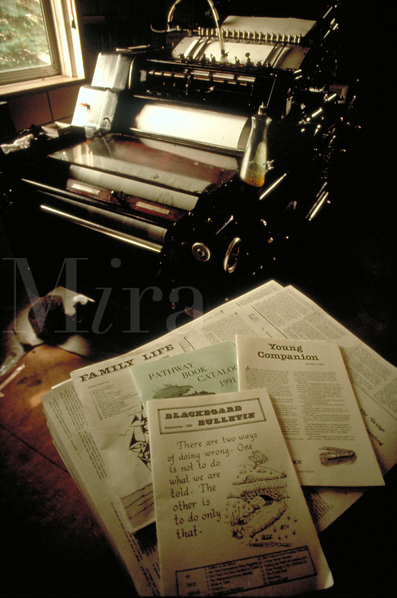 Amish community and religious publications are shown on a table with the hydraulic run printing press in the background at an Amish printing office. Kitchener Ontario Canada Amish printing press.